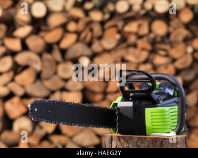 Electric Cordless battery powered chainsaw in front of stacked firewood in the background - Stock Photo