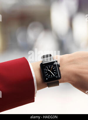 Woman hand with Apple Watch smartwatch on her wrist in outdoor urban scenery isolated on white background - Stock Photo