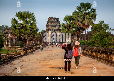 Tourists enter the Angkor Wat temple complex to witness the sunrise in Siem Reap, Cambodia. - Stock Photo