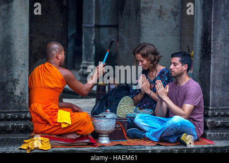 A western couple receive a blessing from a Buddhist monk at Angkor Wat in Siem Reap, Kingdom of Cambodia. - Stock Photo