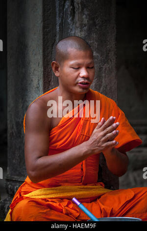 A Buddhist monk sits with his hands clasped and eyes closed chanting prayers in the ancient temple of Angkor Wat, - Stock Photo
