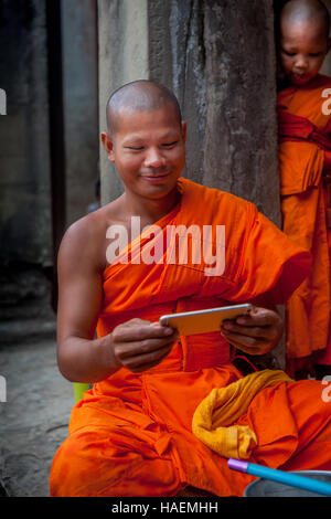 Smiling Buddhist monk in traditional orange robe looking at his smartphone in Angkor Wat temple at Siem Reap, Cambodia - Stock Photo