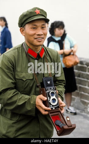 A smiling young Chinese soldier in his simple olive-green army uniform visits the Great Wall of China in the 1980s - Stock Photo