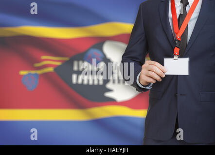 Businessman holding name card badge on a lanyard with a flag on background - Swaziland - Stock Photo