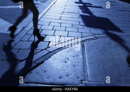 Blue night shadows and silhouette of a woman walking down a New York City sidewalk - Stock Photo