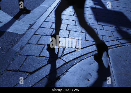 Blue night shadows and silhouette of a woman crossing a NYC street as a man approaches - Stock Photo