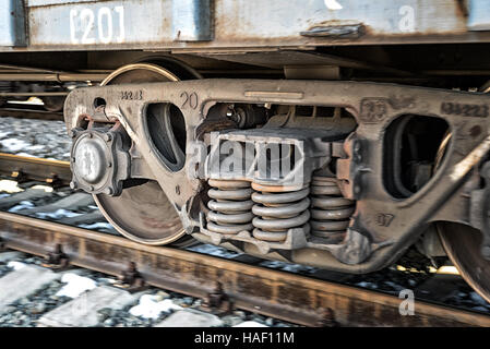 Train wheels of a carriage moving along a train track with slight motion blur - Stock Photo