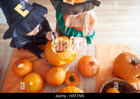 Children carving from the pumpkin - Stock Photo