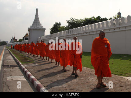 The monk walk outside a wall to enter the Grand Palace to pays respect the The Royal Urn Hall containing the body - Stock Photo