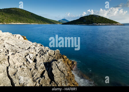 Morning over the rocky coastal area of Cunski with a view to the island of Veli Osir and Osorscica mountain in the - Stock Photo