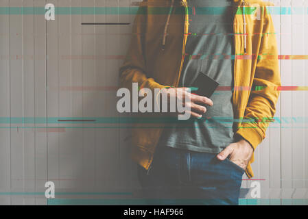 Casual young man posing with mobile phone in hand, technology and lifestyle concept, retro toned image with digital - Stock Photo