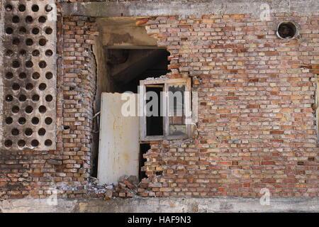 Old destroyed window on brick wall in Sarajevo , Bosnia and Herzegovina - Stock Photo
