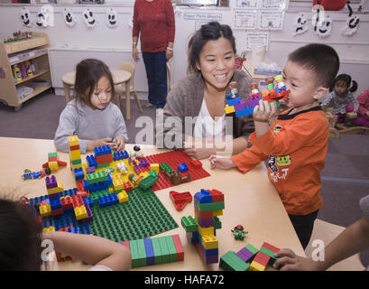 Young children build with Lego blocks at a nursery school in Manhattan in the Chinatown neighborhood on the Lower - Stock Photo