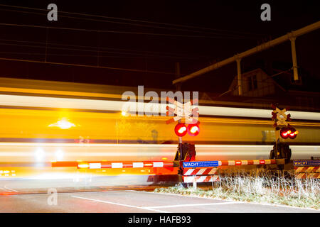 Closed barrier at railway crossing with passing train - Stock Photo