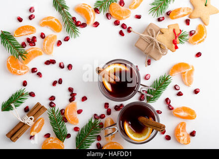 Frame of pomegranate seeds, mandarines and twigs tree with two glasses of hot mulled wine with oranges and spices. - Stock Photo