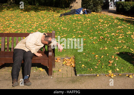 man on bench sleeping and another behind reclines in a London park - Stock Photo