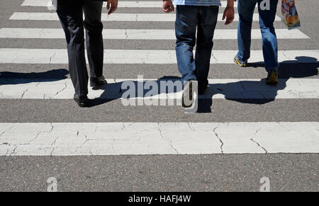 Low Section Of People Walking On Zebra Crossing - Stock Photo