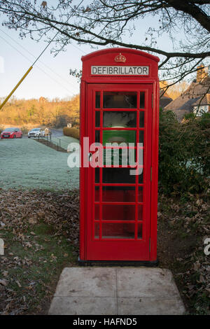 Red telephone box converted to medical defibrillator station in Seale village in Surrey, UK - Stock Photo