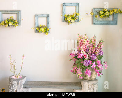 Pink and purple bouquet of flowers in a vase on the white wall - Stock Photo