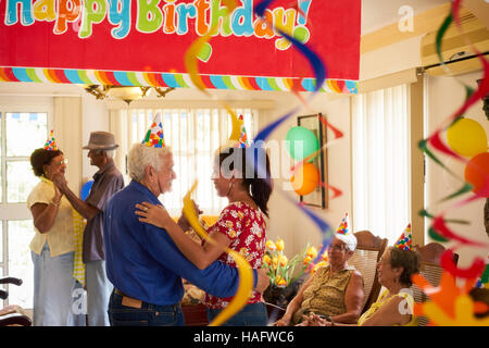 Group of old friends and family celebrating senior man birthday in retirement home. Happy elderly people having - Stock Photo