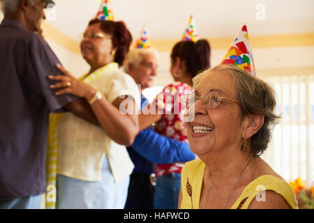 Group of old friends and family celebrating senior birthday party in retirement home. Patient woman smiling in hospice. - Stock Photo