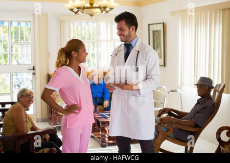 Doctor talking to young woman at work as nurse in hospital for seniors. The man holds a tablet pc. Some elderly - Stock Photo