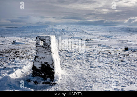 The trig point and summit of a snow covered Pen-y-ghent, one of the Three Peaks, near Settle, North Yorkshire, UK - Stock Photo