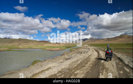 Single female cyclist on the bicycle in the stunning remote part of Western Tibet - Stock Photo