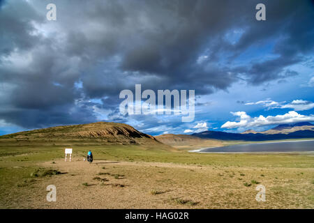 Solo female cyclist on the bicycle in the stunning remote part of Central Tibet - Stock Photo