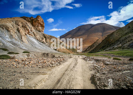 Dirt gravel mountain road through the high central Tibetan plateau, Tibet, China - Stock Photo