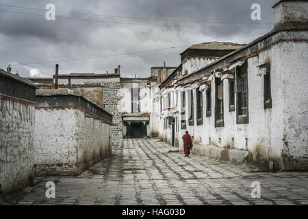Monk walking in the courtyard between buildings in the compound of the Tibetan Monastery in Shigatse in central - Stock Photo