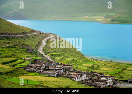 Traditional tibetan homes on the slope of the hill on the shore of the stunning Yamdrok Tso Lake lake in Central - Stock Photo