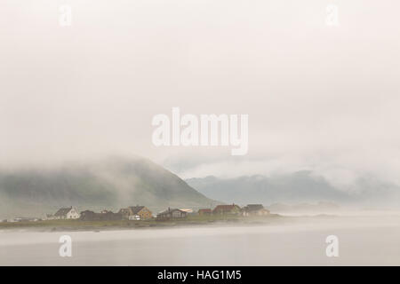 Norway village in clouds of fog on lofoten islands. Cloudy Nordic day. - Stock Photo