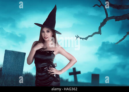 Young asian witch woman with hat standing around in a cemetery at night with moonlight - Stock Photo