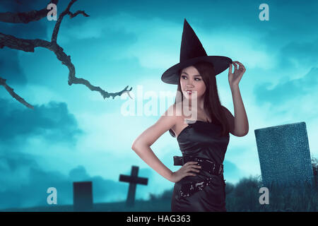 Gorgeous asian witch woman is standing looking his back in a cemetery - Stock Photo
