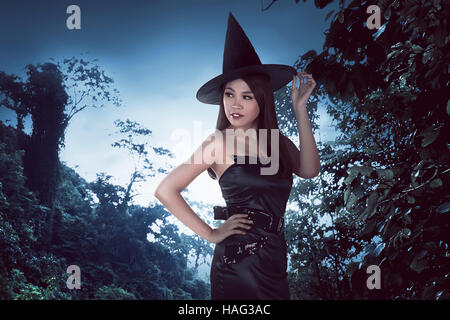 Beautiful young asian woman in witches costume and holding his hat on the forest background - Stock Photo