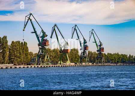 Port cranes for unloading sand on ship. - Stock Photo