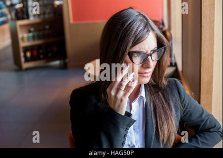 Businesswoman talking on the phone and frowns - Stock Photo