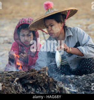 A Burmese mother and daughter cooking a fish on Nagapali Beach in Rakhine State in Myanmar (Burma). - Stock Photo