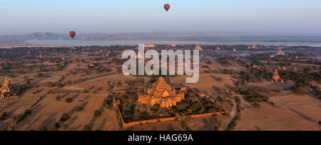 Hot air balloons flying over the temples of the Archaeological Zone in Bagan in the early morning sunlight. Myanmar. - Stock Photo