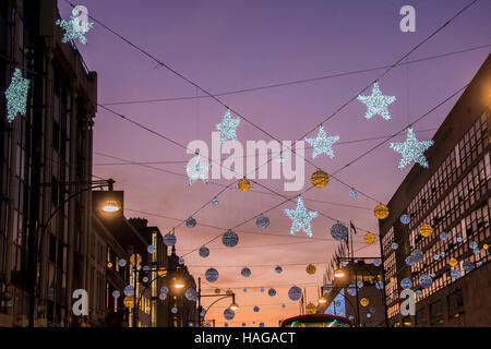 London, UK. 30th Nov, 2016. Christmas lights in a busy Oxford street as the sun sets. London 30 Nov 2016 Credit: - Stock Photo