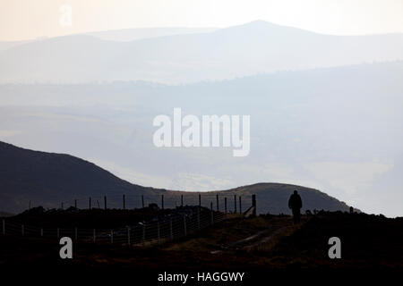A lone hill walker walking along Offas Dyke Path in the Clwydian Range in Denbighshire, North Wales. - Stock Photo