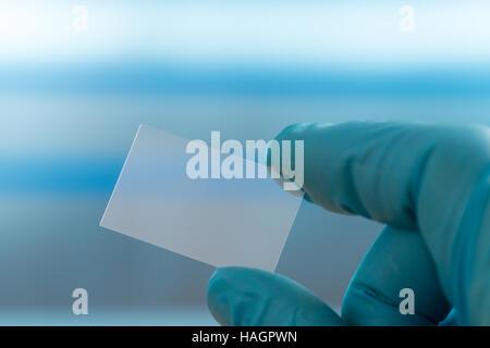 Empty microscope slide in hand - Stock Photo
