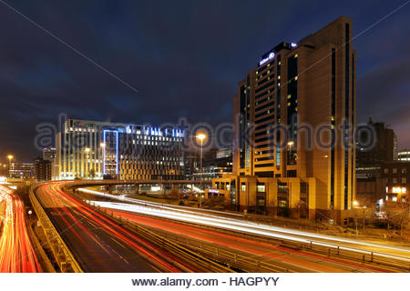Car night trails heading to and from Glasgow city centre with the Hilton hotel and Scottish power buildings in view - Stock Photo