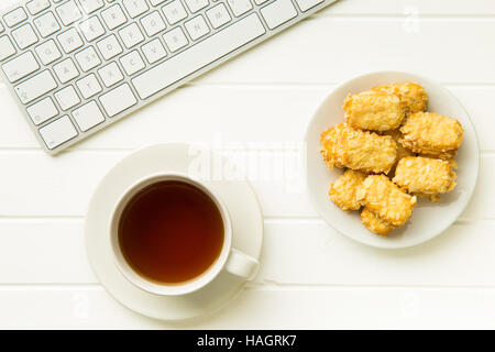 Break for tea and almond biscuits at the office. Concept with tea,cookies and computer keyboard. - Stock Photo