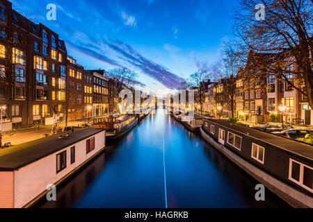 Canal with House Boats in Amsterdam Netherlands - Stock Photo