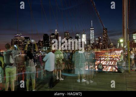 Tourists on Brooklyn Bridge admire downtown Manhattan at sunset (long exposure), New York, United States. - Stock Photo