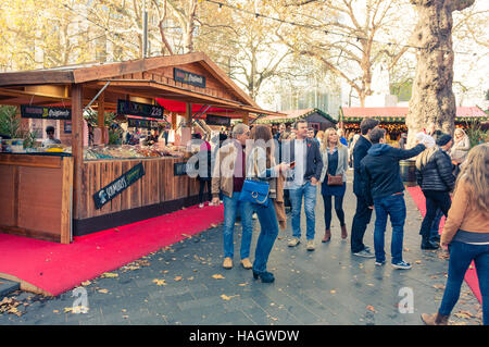 Visitors standing in front of the Bavarian style huts at the Christmas Market in Leicester Square, 2016, London, - Stock Photo