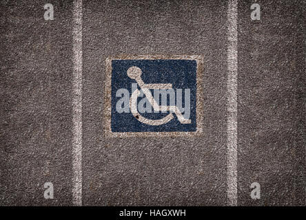 wheelchair parking symbol on asphalt car park - Stock Photo