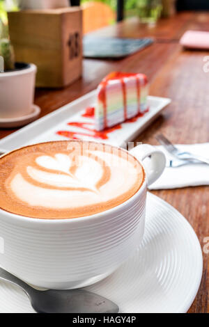 Cup of hot latte art coffee on wooden table - Stock Photo